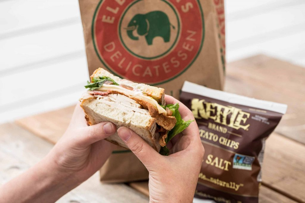Elephants Delicatessen sack lunch with sandwich, bag, and Kettle chips