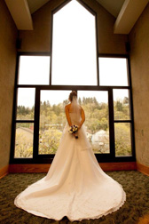bride in a wedding dress looking out the window