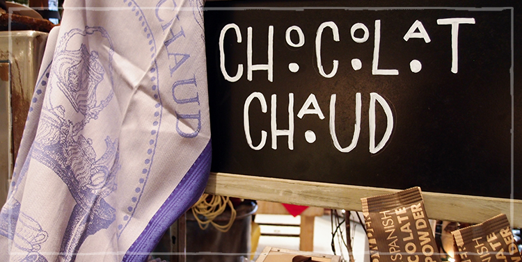 "Chalkboard at Elephants Deli with the words ""Chocolat Chaud"" over a display of packets of chocolate powder"
