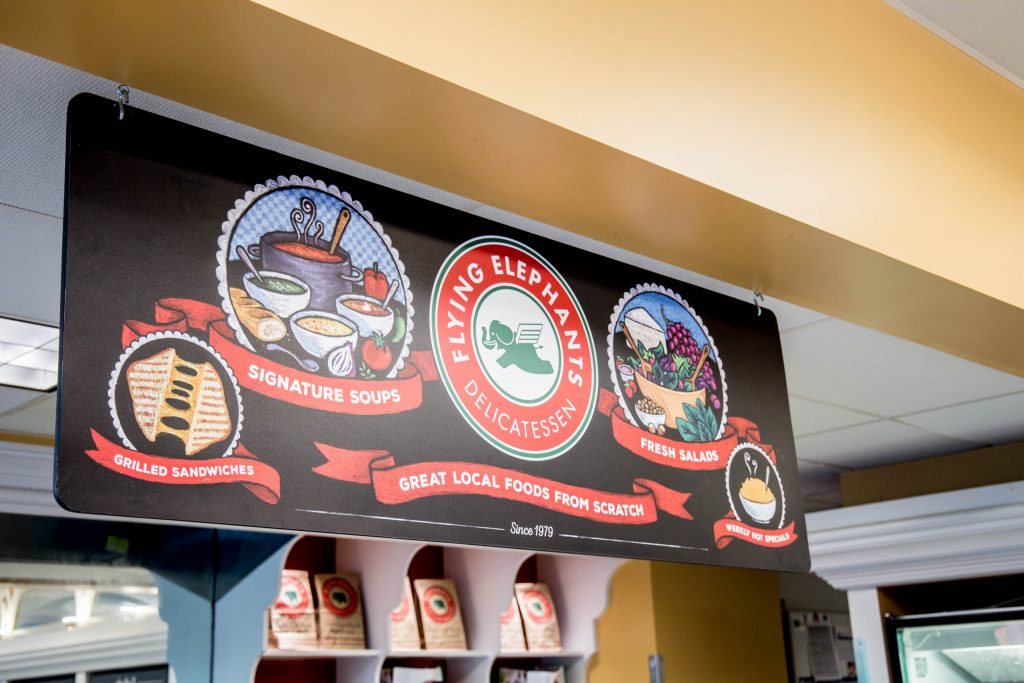 location signage with chalkboard food pictures and Elephants logo at Elephants Delicatessen Kruse Way