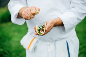 Action shot of a chef squeezing lime onto a taco