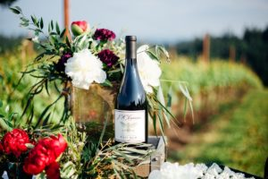 Bottle of red wine sitting on a table with flowers in a vineyard
