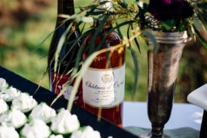 Bottle of rosé sitting on a table with flowers in a vineyard