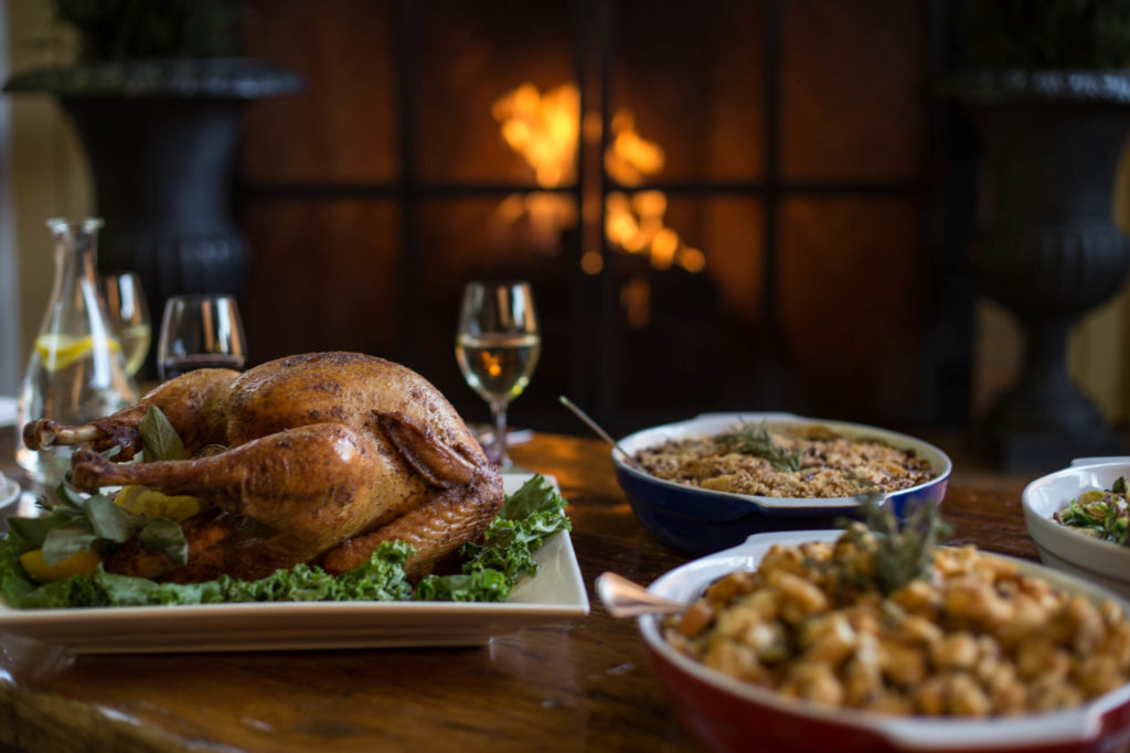 Turkey and sides for Thanksgiving on a table in front of a fire place