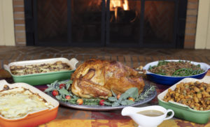 table packed with thanksgiving food with fireplace in the background